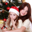 Mother and daughter holding cat over Christmas tree — Stock Photo