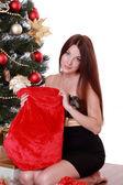 Woman sitting over Christmas tree — Stock Photo