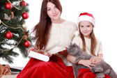 Mother and daughter holding cat over Christmas tree — Foto Stock