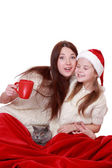 Mother and daughter holding cat over Christmas tree — Stockfoto