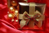 Gift box with golden christmas balls — Stock Photo