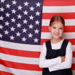 Stock Photo: Schoolgirl standing against Americflag