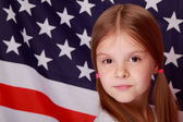 Little girl on the background of the American flag — Stock Photo