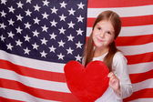 Girl on the background of the American flag — Stock Photo