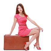 Woman sitting on old suitcase — Stockfoto