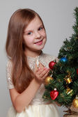 Child decorates a Christmas tree — Stock Photo