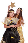 Sisters in fancy dress holding a golden moon and a star — Foto de Stock