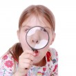 Girl looking through a magnifying glass — Stock Photo #40304001