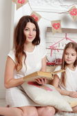 Mother and her daughter with book — Stock Photo