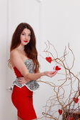 Beautiful girl decorates branches — Stock Photo