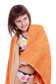 Girl in swimsuit holding orange towel — Stock Photo