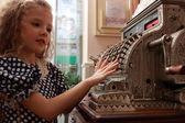 Menina e uma velha caixa registradora — Fotografia Stock