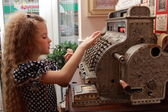 Girl and an old cash register — Stockfoto