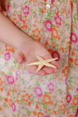 Girl holding starfish — Stock Photo
