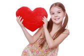 Girl hugging a large red heart — Stock Photo