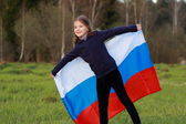 Girl holding a large Russian flag — 图库照片