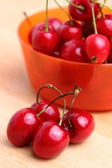 Sweet cherries in orange plastic bowl — Stock Photo