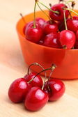 Sweet cherries in orange plastic bowl — Stok fotoğraf