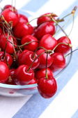 Ripe sweet cherries in bowl on tablecloth — Stok fotoğraf
