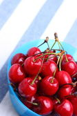 Ripe sweet cherries in bowl on tablecloth — ストック写真