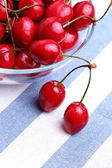 Ripe sweet cherries in glass bowl on tablecloth — Стоковое фото
