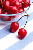 Ripe sweet cherries in glass bowl on tablecloth — Stok fotoğraf