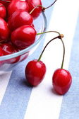 Ripe sweet cherries in bowl on tablecloth — Stock Photo