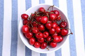 Ripe sweet cherries in bowl on tablecloth — Stockfoto