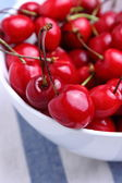 Ripe sweet cherries in bowl on tablecloth — Foto de Stock
