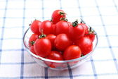 Cherry tomatoes in glass bowl on tablecloth — Stock fotografie