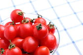 Cherry tomatoes in glass bowl on tablecloth — Stock Photo