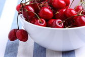 Red cherries on a blue tablecloth — Stock Photo