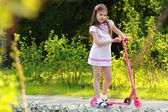 Küçük kız sürme scooter — Stok fotoğraf