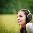 Portrait of a pretty young woman listening to music on her mp3 p — Stock Photo #10408499