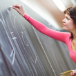 Pretty young teacher writing on the chalkboard — Stock Photo