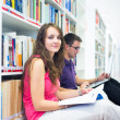 Two college students in library — Stock Photo