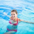 Portrait of a young woman relaxing in a swimming pool — Stock Photo #12428206