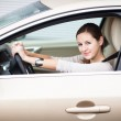 Pretty young woman driving her new car — Stock Photo #12428314