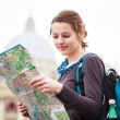 Pretty young female tourist studying a map — Stock Photo #12428329