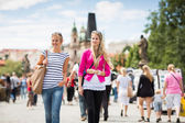 Two female tourists walking along the Charles Bridge — Stok fotoğraf
