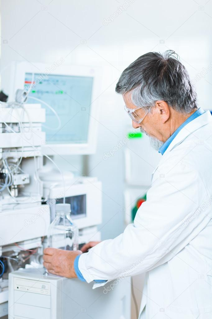 Senior male researcher carrying out scientific research in a lab (shallow DOF; color toned image) — Stock Photo #12427396