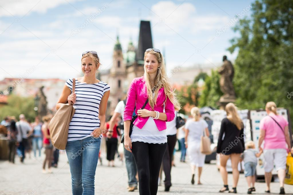 Two female tourists walking along the Charles Bridge while sightseeing in Prague, the historical capital of the Czech Republic (color toned image; shallow DOF)  Stock Photo #12427961