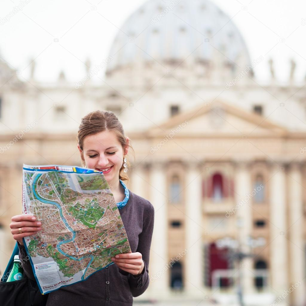 Pretty young female tourist studying a map at St. Peter's square in the Vatican City in Rome — Stock Photo #12428331