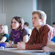 Young, pretty female college student sitting in a classroom full — Stock Photo #12662914