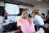 Young, pretty female college student sitting in a classroom full — Stock Photo