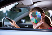 Young female driver playing music in the car (changing CDs) — Стоковое фото