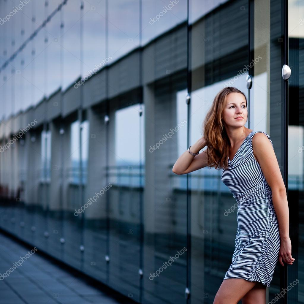Young woman posing inside a modern top architecture building complex (shallow DOF, color toned image)  Stock Photo #12662348