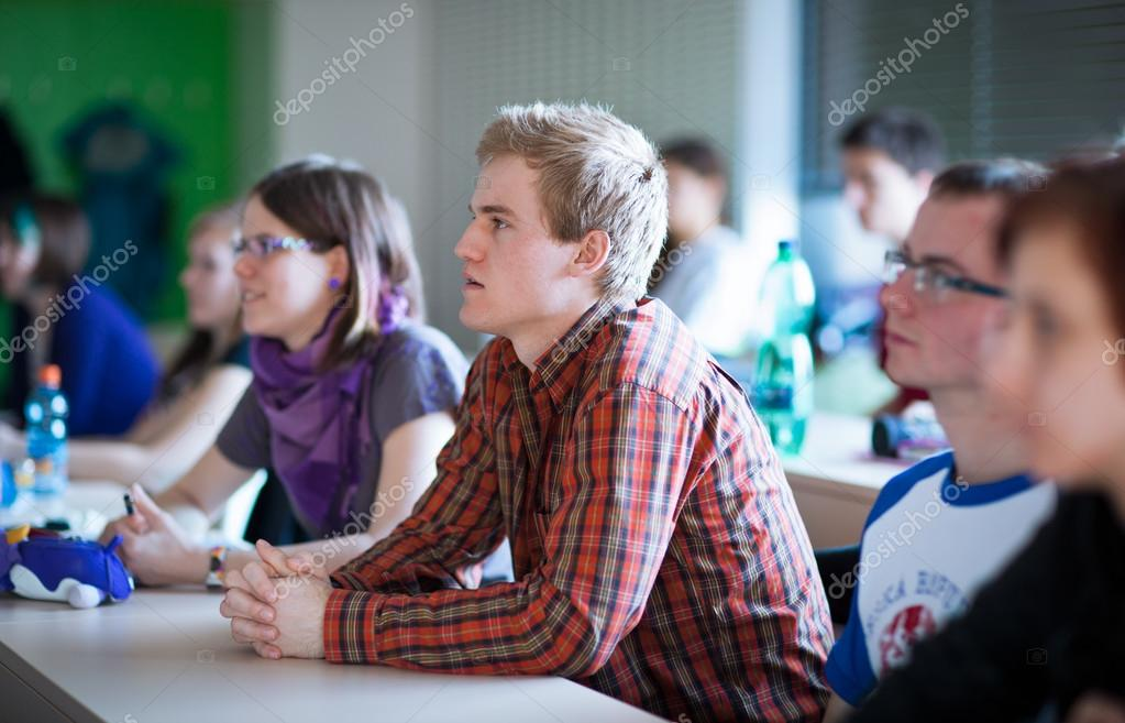 Young, handsome college student sitting in a classroom full of students during class — Stock Photo #12663036