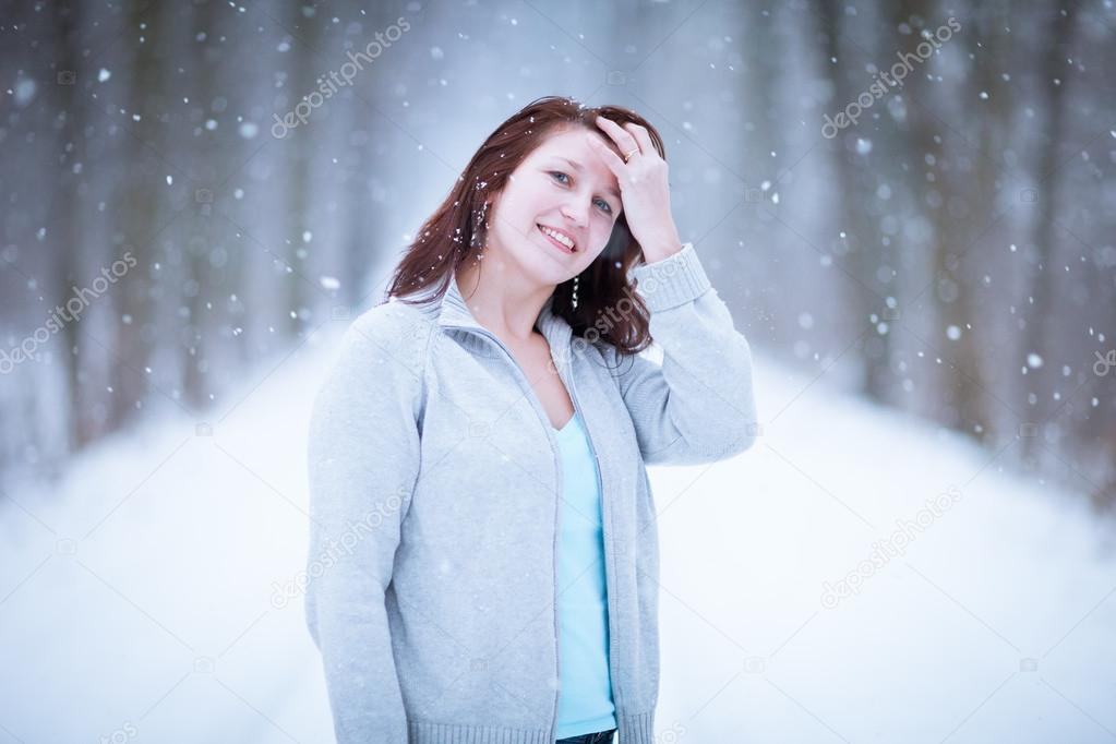 Enjoying the first snow: young woman outdoors on a lovely forest path watching the snowflakes falling (color toned image)  Stock Photo #12663478