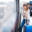 Pretty young woman at a train station — Stock Photo #17128603